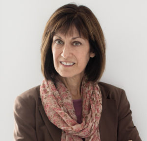 Photo of Margaret Kamitsuka in a brown blazer with a dusty pink scarf, shoulders facing camera